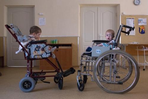 В интернате, даже таком хорошем, как восьмой, за всем не уследишь, всех не обеспечишь; вот и сидят пятилетние детки в колясках для более старшего возраста: колясок для малышей не всем хватает…