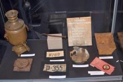Самовар, личные номера на  одежде, форма для выпечки хлеба,  миска, кованный гвоздь, портрет  Сталина. Быт узников ГУЛАГа; Международный Мемориал.