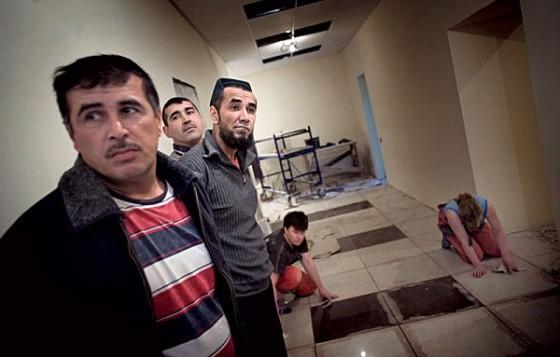 """Задержанные рабочие-нелегалы ждут, пока девушки-молдаванки доложат плитку, — чтобы затем отправиться в спецприемник Фотография: Юрий Козырев/NOOR для """"РР"""""""