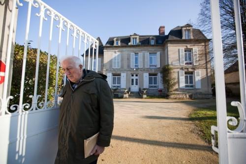 Жан Ванье у ворот своего дома в Троли. Троли -- это не специализированное поселение, а обычная деревня на севере Франции. В ней живут 2200 жителей. 10% из них - умственно отсталые, 7% -- те, кто им помогает, а остальные 83% -- самые обычные люди