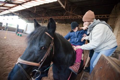 Сеанс иппотерапии. Чтобы один неходячий человек мог удержаться на лошади, ему должны помогать не менее трех ассистентов