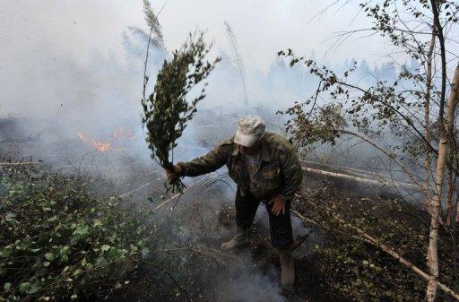 Доброволец помогает тушить пожар
