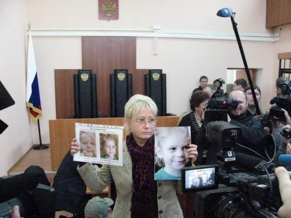 Лариса Агеева с фотографиями Глеба в суде