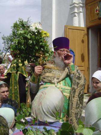Сложив руку рупором у рта, батюшка Сергий после крестного хода просит народ молиться о здравии новорожденного младенца Савеллия, который лежит в реанимации