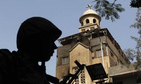 Солдат, стоящий на страже возле церкви Святой Марии, которая была подожжена во время столкновений между мусульманами и христианами 8 мая в районе Гиза в Имбаба (фото: Reuters)