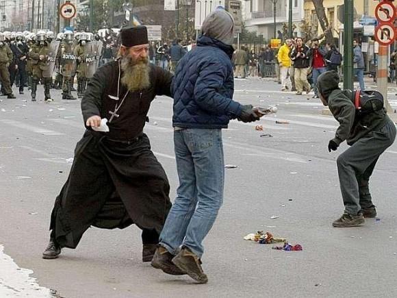 Греческий священник пытается остановить учинителя беспорядков от того, чтобы бросить бутылку с зажигательной смесью в полицию