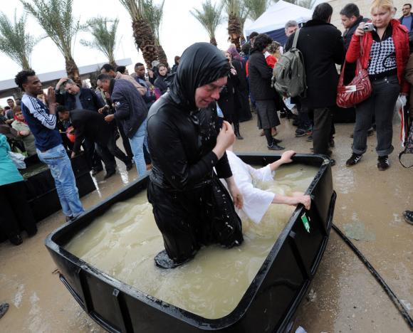 Греческая монахиня погружается в купель с водой из Иордана ups.com