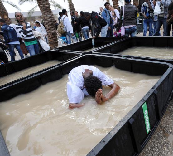 Христианин из Эфиопии погружается в купель с водой из Иордана ups.com