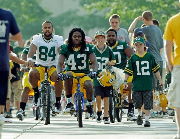 Футболисты едут на тренировку на детских велосипедах. США, 2011 год