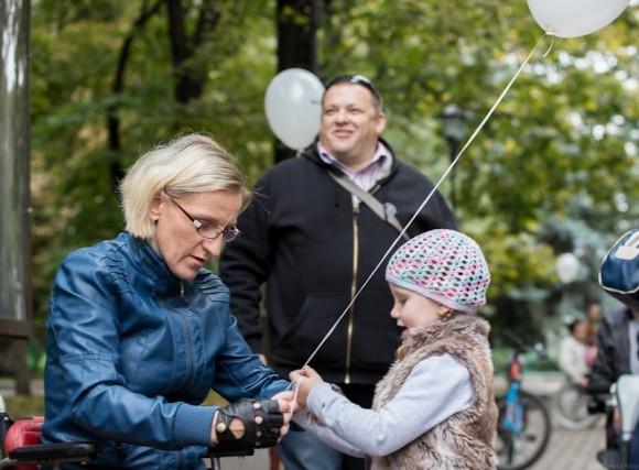 Мама-инвалид привязывает дочке на руку воздушный шарик, чтобы он не улетел