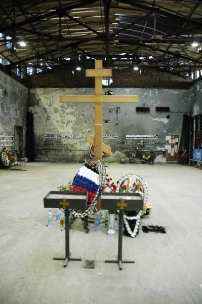 Поклонный крест, установленный в центре спортивного зала. Его два раза устанавливали и два раза ломали родители детей, погибших в теракте. На полу до сих пор видны темные пятна от крови.