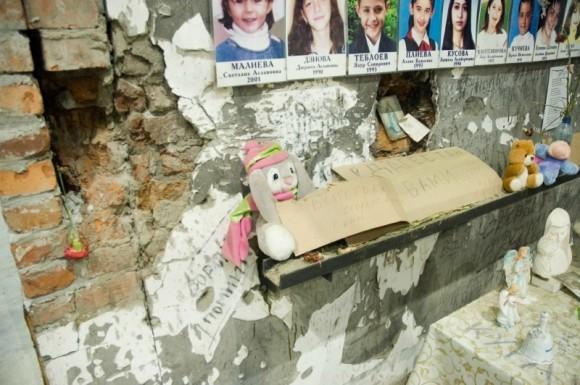 На стенах спортзала фотографии детей, памятные надписи, на полу цветы, конфеты, игрушки, вода, свечи, ангелочки.