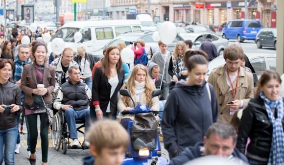 Процессия в инвалидных колясках и их сопровождающие занимают почти все пространство неширокого тротуара на Тверской
