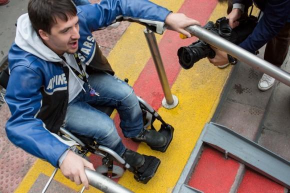 Артур Смольянинов пытается спуститься вниз по специальным рельсам. Однако у него ничего не получается: размер коляски и колес не совпадает с колеёй, спуск слишком крутой. «Ну нет, - говорит он, - голова у меня одна, а тут ее и свернуть недолго»