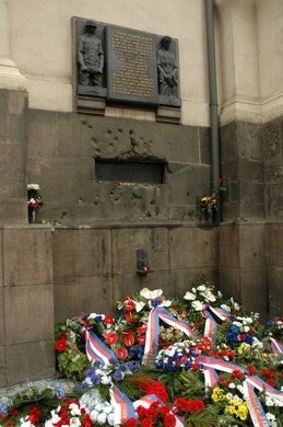 Памятная доска с символической фигурой парашютиста и владыки Горазда и со следами от немецких пуль