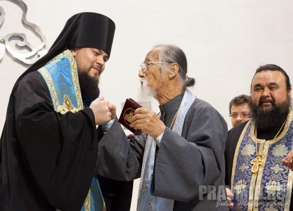 владыка Ефрем вручает памятный знак прот. Михаилу Ли