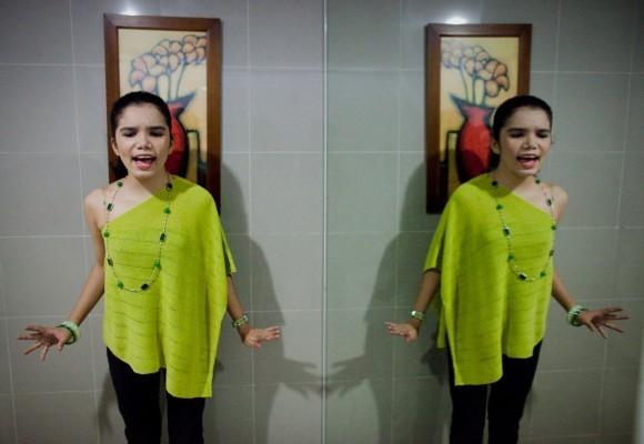 Тара Мари Сантьяго, страдающая аутизмом, репетирует в туалете, прежде чем выйти на сцену во время бесплатного публичного концерта Autismusical, на котором люди, страдающие этой болезнью, могут продемонстрировать свои таланты, во время Всемирного дня распространения информации об аутизме в Кесон-Сити, Филиппины, 2 апреля 2009.