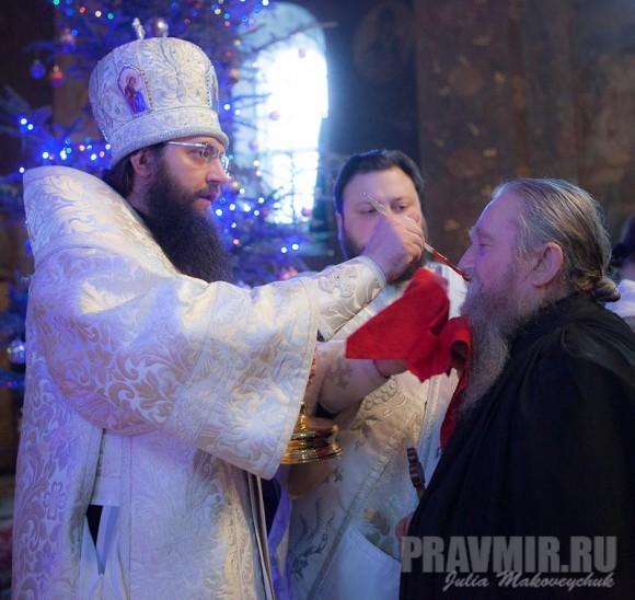 Епископ Климент причащает схимонаха — насельника Киево-Печерской лавры.