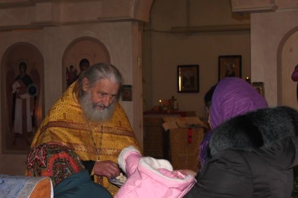 После литургии отец Игорь раздает всем кусочки просфоры