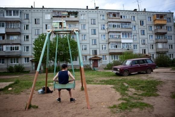 Мальчик катается на качелях во дворе, Сыктывкар, 2011