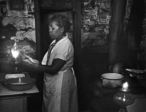 Мод готовится к работе на кухне, при свете лампы.