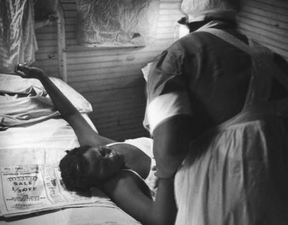 Корчась от жуткой боли, семнадцатилетняя мать шепчет молитвы, а миссис Гадсден держит ее за руку.