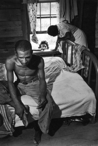 33-летний Леон Бекасов, у него туберкулез. Он сидит на кровати, пока Мод с его сестрой собирают больного в госпиталь.