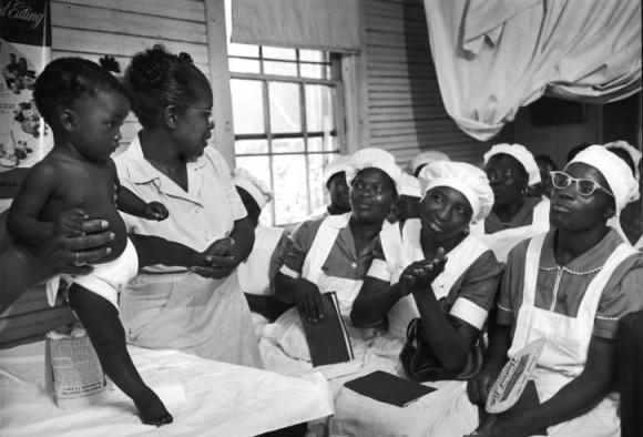 Обучение класса акушерок. Мод показывает, как обследовать ребенка на наличие дефектов. Мод обучает 4 класса, готовя в год примерно 12 акушерок.