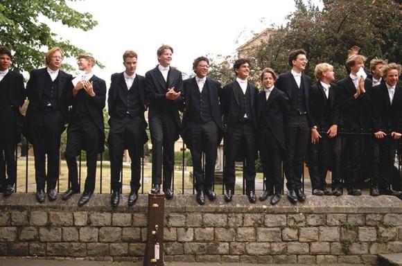 Мальчики из Колледжа Итон забрались на забор, чтобы получше рассмотреть Её Величество королеву Елизавету II во время её визита в учебное заведение в 1990 году.