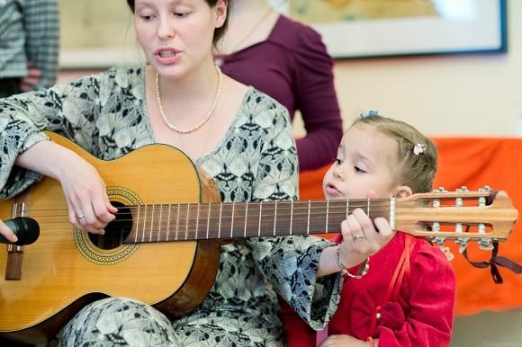 Дочка Юревичей Ася играет на гитаре. Внучка Олечка помогает