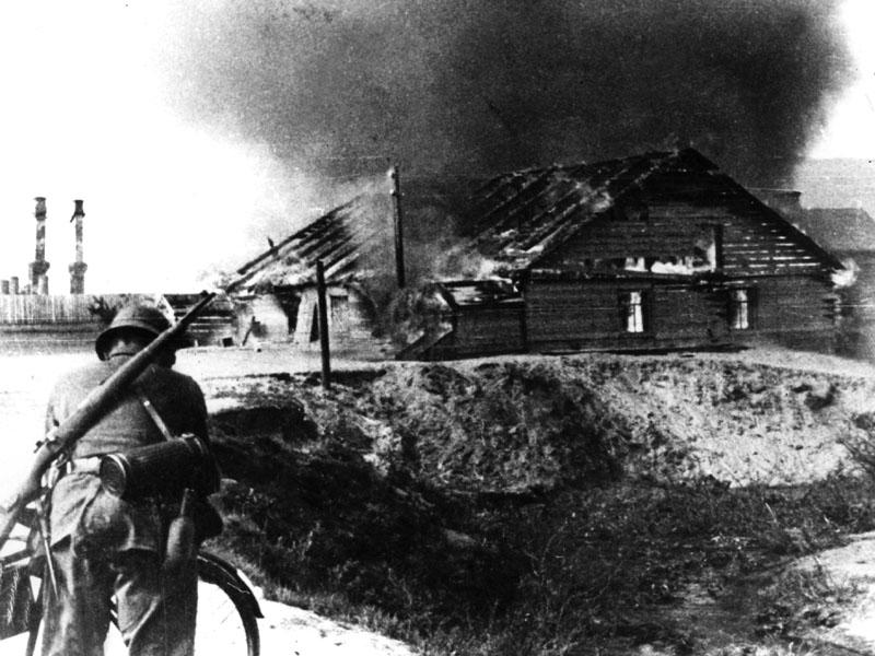 Гитлеровец поджигает дома в деревне