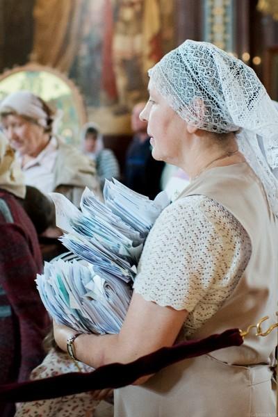 Работница Храма собрала заполненные записки и несет их к месту молебна