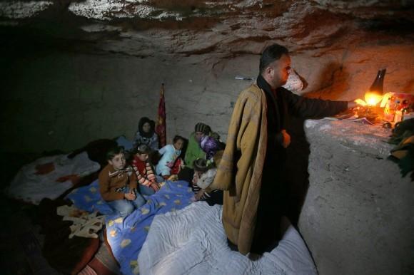 Бывший сирийский полицейский Аднан аль-Хамод внутри подземного убежища, которое он сделал при помощи отбойного молотка, чтобы защитить свою семью от обстрелов и авиаударов.