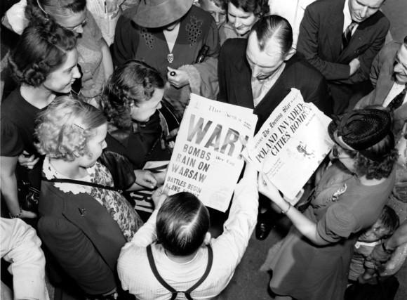 Толпа читает газетные заголовки «Дождь бомб на Варшаву» возле здания Госдепартамента США
