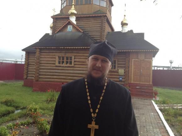 Отец Александр Левин на фоне храма в колонии. Фото о. Александра Пелина