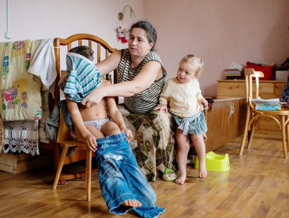 Коля – пятый ребенок в семье – примеряет одежду. Ведь за лето Коля очень вырос