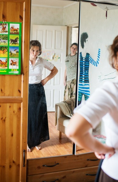 Оля готовится к школе у шкафа с одеждой – ведь в этом году введена обязательная школьная форма