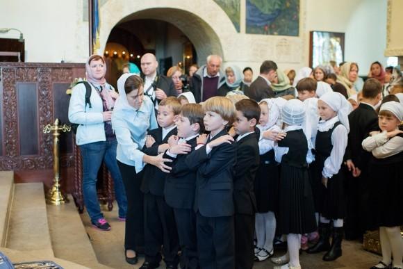 Учительница первого класса помогает ребятам встать друг за другом