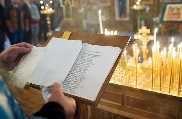 Отец Георгий читает имена всех погибших – сначала тех, кому не было 12 лет, потом подростков, потом – взрослых. В руке  у него стакан с водой, потому что иногда голос его сбивается