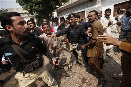Angry Christian men push a policeman out of a church after a blast in Peshawar