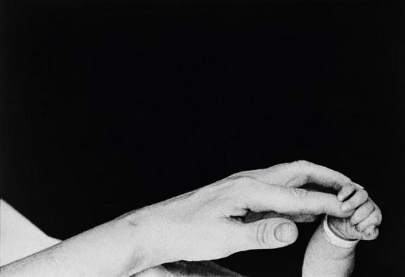 Ева Арнольд. США. Нью-Йорк. Лонг-Айленд. Мать держит руку только что родившегося ребенка, Порт Джефферсон. 1959 год