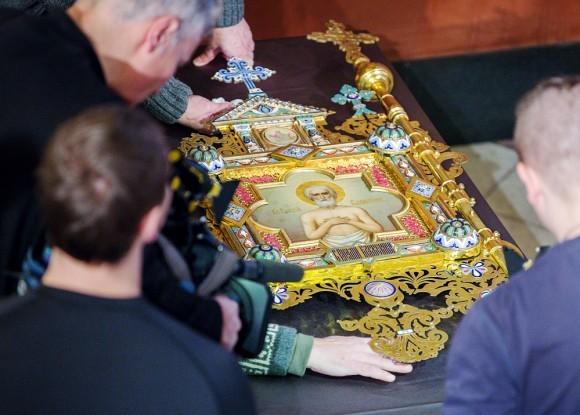 Реставраторы выносят хоругвь с изображением блаженного Василия