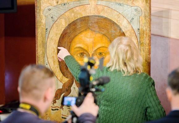Реставратор иконы показывает те фрагменты, где была проведена реставрация