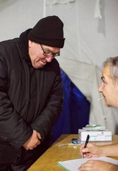 В палатке у входа стоит стол. За ним работник социальной службы записывает имя-фамилию и дату рождения каждого пришедшего