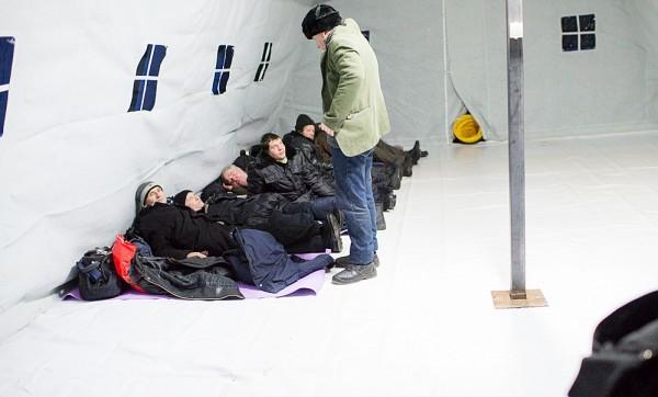 Но очень скоро работник соцслужбы просит всех устраиваться плотно, так, чтобы между ковриками не оставалась свободного места — уже сейчас становиться понятно, что народу будет много. Уже в прошлую ночь в палатке, рассчитанной на 50 человек, ночевало 75