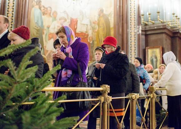 Женщина привязывает веревочку к крестику — готовится приложить его к Дарам