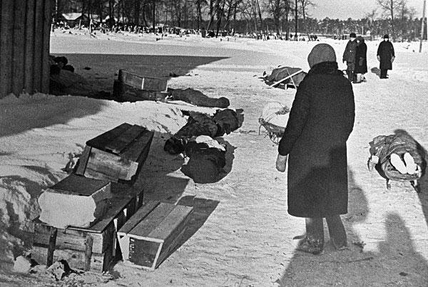 1 февраля 1943г. Женщина стоит рядом с телами умерших и гробами для их погребения.