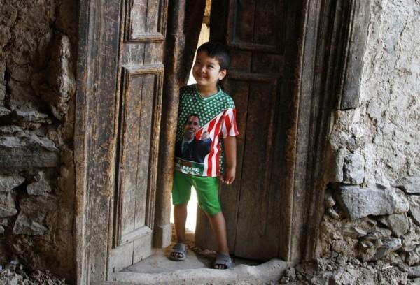 Афганский мальчик в футболке с изображением американского президента Барака Обама выглядывает из-за дверей своего дома в старом районе Кабула, 23 июля 2013 года. (AP Photo / Ахмад Джамшид)
