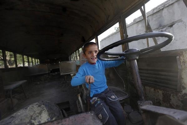 20.Афганский мальчик сидит за рулем развалившегося автобуса советских времен в Кабуле, 9 мая 2011 года. (AP Photo / Мустафа Курайши)