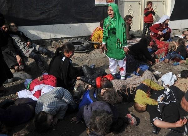 12-летняя Тарана Акбари кричит, стоя рядом с людьми, убитыми и ранеными в результате действий террориста-смертника, убившего более 70 гражданских во время религиозной церемонии в храме Абул Фазел в центре Кабула, где шииты праздновали день Ашуры, 6 декабря 2011 года. Фотограф агентства Франс-Пресс, Массуд Хуссейни, получил Пулитцеровскую премию  для агентства за снимок 16 апреля 2012 года в категории «фотографии последних новостей» - «за его разрывающий сердце снимок с девочкой, кричащей от страха, после взрыва террориста-смертника в заполненном кабульском храме». (Массуд Хуссейни / AFP / Getty Images)